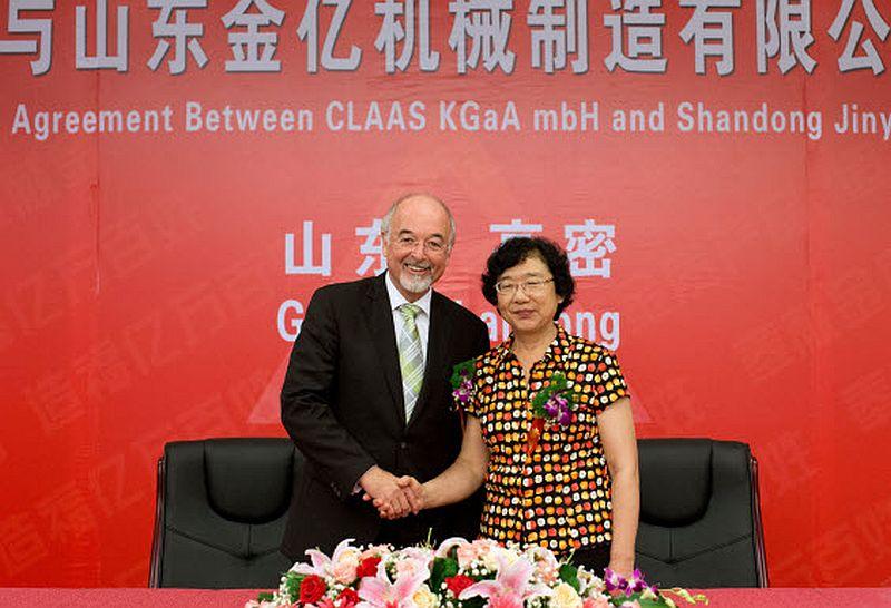 """דר' תיאו פריי, דובר קלאאס, לוחץ את ידה של ז'ין-זינג מה, יו""""ר ג'ין-ג'י הסינית בעת החתימה על הסכם הרכישה"""