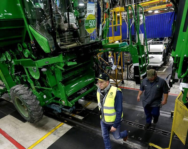 אולסן צועד נרגש לאורך פס ייצור הקומביינים של ג'ון דיר במפעלה במולין